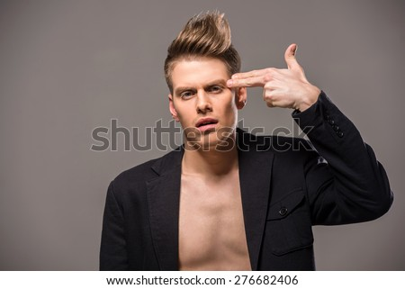 Young handsome man in tuxedo holding fingers on her head on dark background. Fashion portrait. - stock photo
