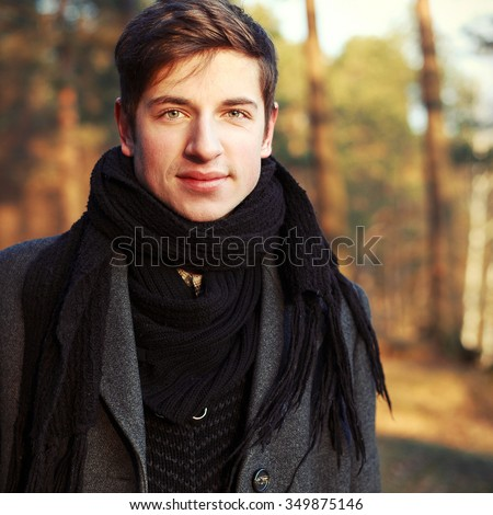 Young handsome man in winter coat posing in the park smiling having fun  - stock photo