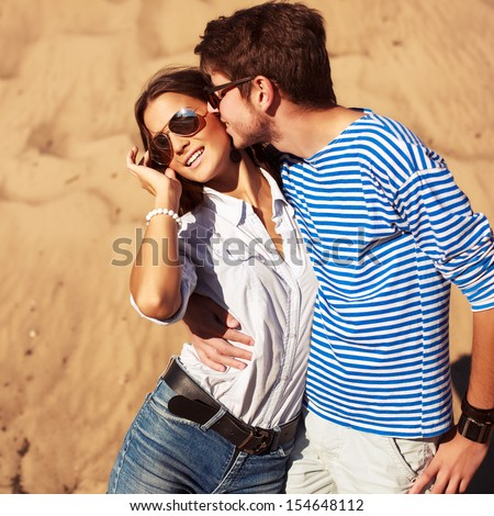 Young handsome man kissing pretty brunette in summer on vacations. Happy free emotions.  - stock photo