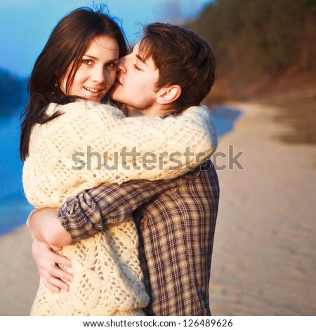 Young handsome man kissing pretty girl outdoors. Attractive couple outdoor spring sunny portrait - stock photo