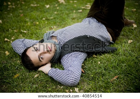 Young handsome man laying on grass staring at camera - stock photo