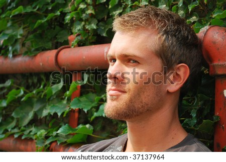 Young handsome man leaning against wall - stock photo