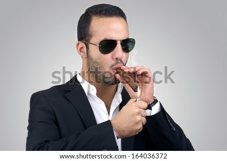 Young handsome man lighting a cigar