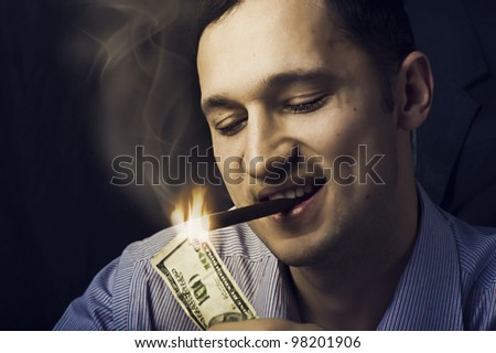 Young handsome man lighting his cigar with $100 note - stock photo