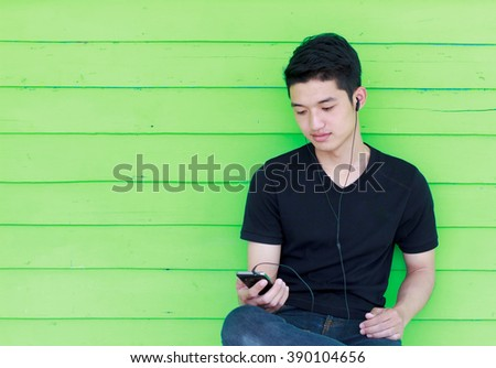 Young handsome man listening to the music on his portable mp3 player outside the room (color toned image)  - stock photo