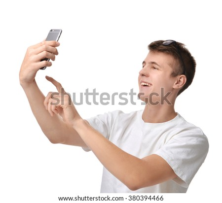 Young handsome man looking at smartphone and taking selfie isolated on a white background