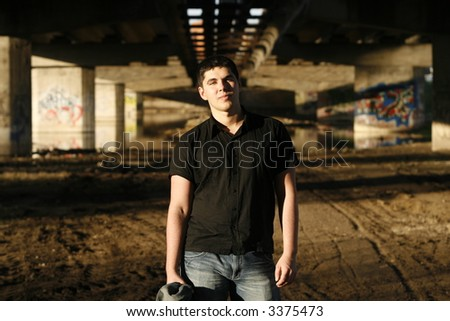 young handsome man looking provocatively, walls covered with graffiti on his background
