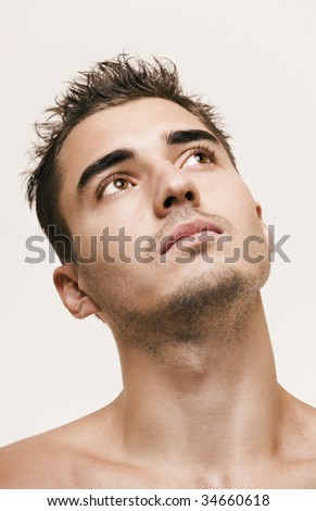 Young handsome man looking up portrait - stock photo