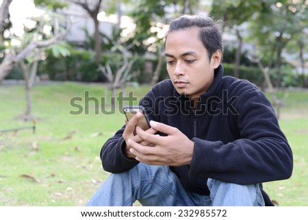 Young handsome man making a call on his mobile sitting in grass on green field. - stock photo