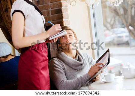 Young handsome man making order at restaurant - stock photo