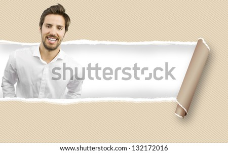 young handsome man on a torn paper background to place your concept - stock photo