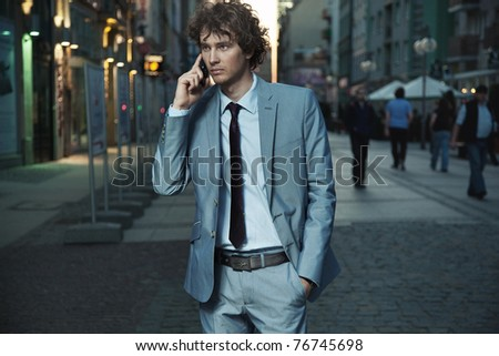 Young handsome man on evening city street - stock photo