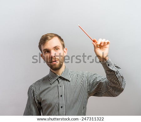 Young handsome man one hand with a pencil in. Gesture. On a gray background - stock photo