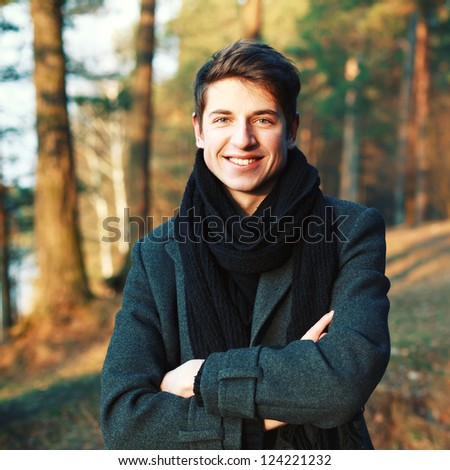 Young handsome man outdoor portrait. Smiling guy with attractive smile. - stock photo