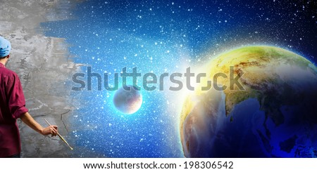 Young handsome man painter with brush in hand. Elements of this image are furnished by NASA - stock photo
