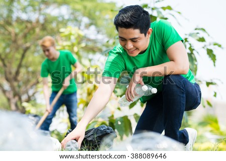 Young handsome man picking up litter in the forest