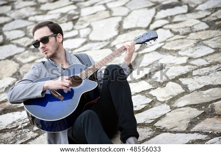 Young handsome man playing guitar in urban background - stock photo