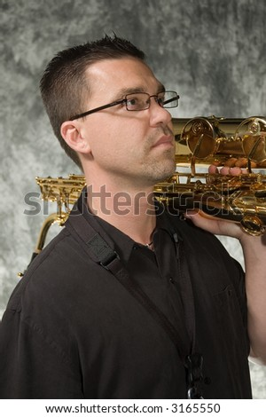young handsome man posing in front of portrait backdrop with saxaphone