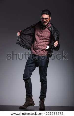 Young handsome man pulling his black leather jacket while looking at the camera. Full body image. - stock photo