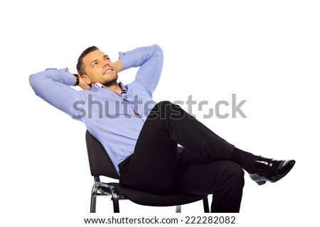 Young handsome man relaxing on a chair isolated over white background - stock photo