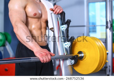 Young handsome man sits after workout in the gym - stock photo