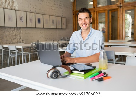 young handsome man sitting at table in co-working office, working at laptop, work place, smiling, happy, positive mood