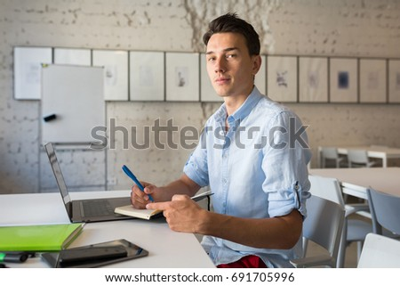 young handsome man sitting at table in co-working office, working at laptop, work place, writing diary book