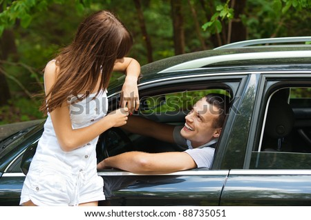 young handsome man sitting car looking out window talking beautiful young woman background summer green park - stock photo
