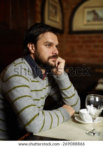 Young handsome man sitting in a restaurant and drinking coffee