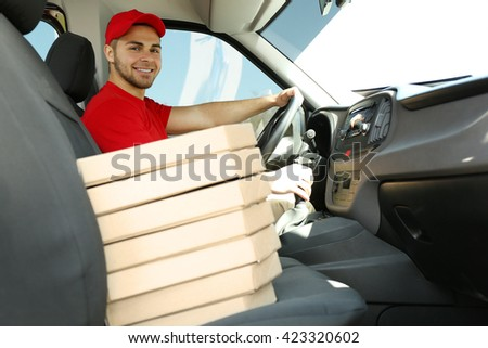 Young handsome man sitting in car with pizza - stock photo
