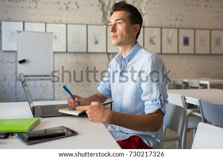young handsome man sitting in office at table, working on laptop, casual style, shirt, freelancer, writing notes in notebook, thinking
