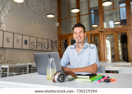 young handsome man sitting in open space office at table, working on laptop, casual style, shirt, freelancer, smiling, happy, workplace