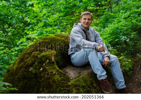 Young handsome man sitting on a rock in the forest