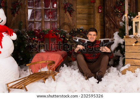 Young Handsome Man Sitting on the Floor with Cotton Snow in Winter Showing Ice Skates Surrounded by Beautiful Christmas Decors at the Wooden House. - stock photo