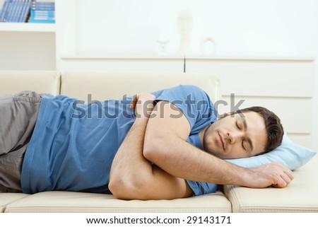 Young handsome man sleeping on couch at home, side view. - stock photo