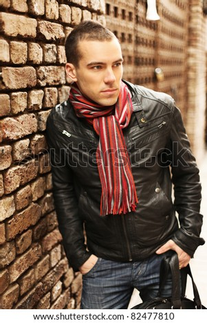 young handsome man standing against old brick wall