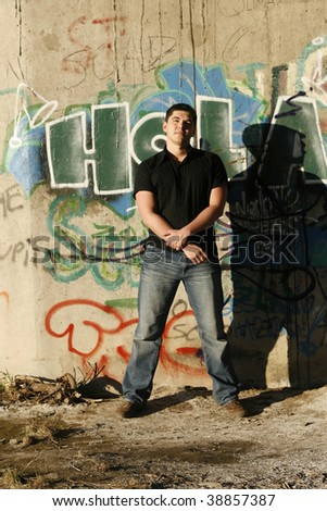 Young handsome man standing by the wall with Spanish graffiti on it