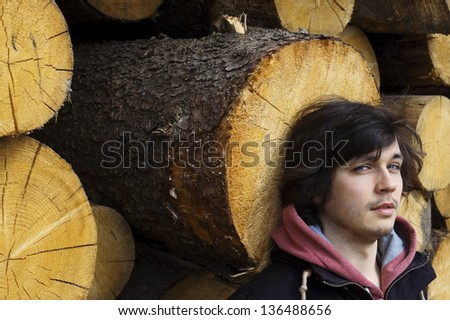 Young Handsome Man Standing near Tree Trunks Outdoors - stock photo