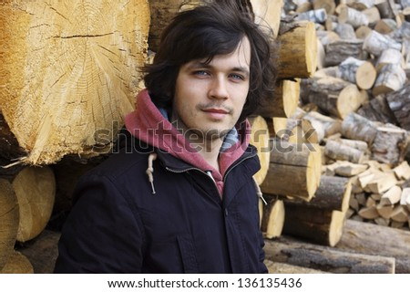 Young Handsome Man Standing near Wooden Logs - stock photo