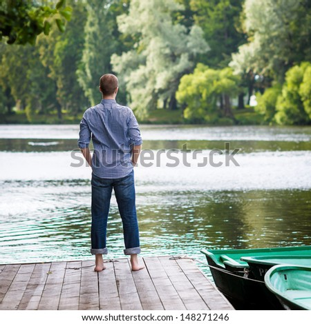 Young handsome man standing on wooden pier, relaxing and meditating in summer morning, back view - stock photo