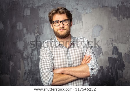 Young handsome man standing with crossed arms - stock photo