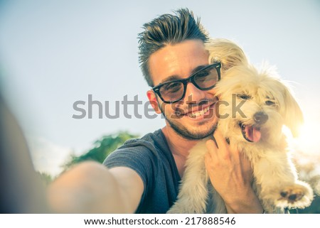 Young handsome man taking a selfie with his dog - stock photo