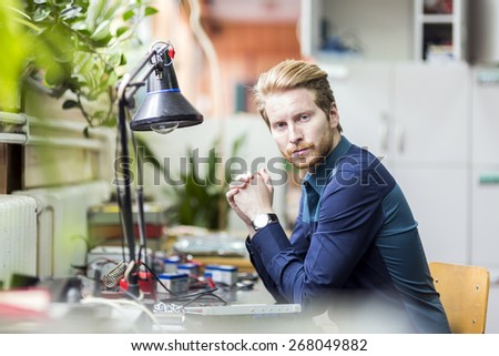 Young handsome man thinking how to solder the circuit board and fix it - stock photo