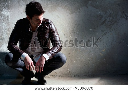 Young, handsome man thinking, sitting on the floor - stock photo