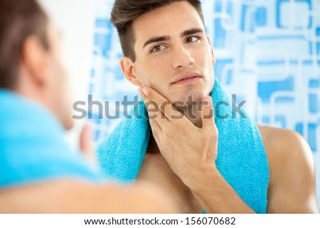 Young handsome man touching his smooth face after shaving - stock photo