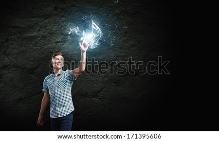 Young handsome man touching music clef icon - stock photo