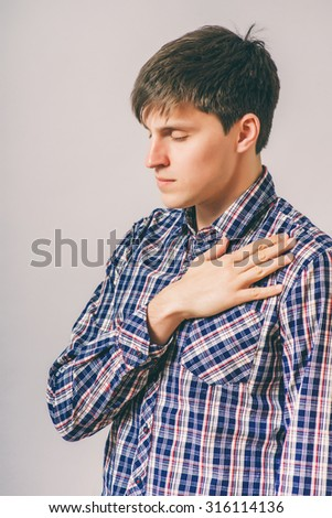 Young handsome man upset keeps his heart, hands on heart. Gesture. On a gray background - stock photo