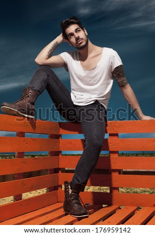 young handsome man wearing jeans posing for camera - stock photo