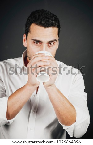 Young handsome man with beard and mustache drinking coffee, studio portrait