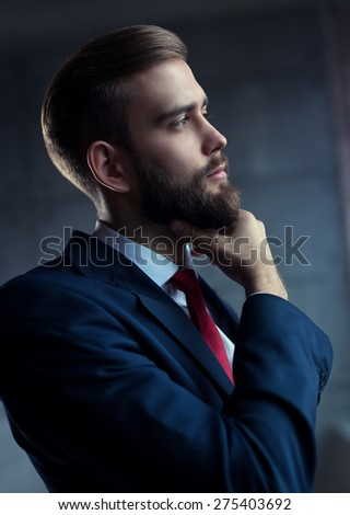 Young handsome man with beard in black suit in pensive pose looking outside to window. - stock photo